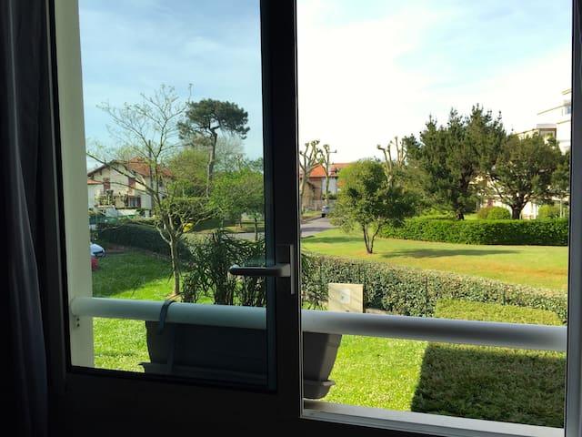 Vue depuis la fenêtre sur le parc de la résidence