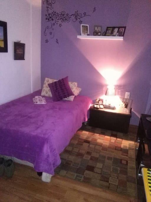 Dormitorio con cama matrimonial, ropero, tv, ventanal y acceso al baño