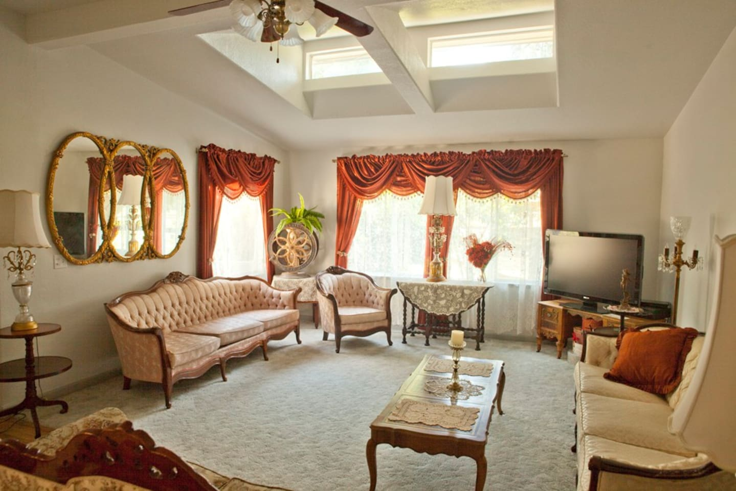 The living room features vintage and reproduction furniture in a skylit room overlooking horse pastures.