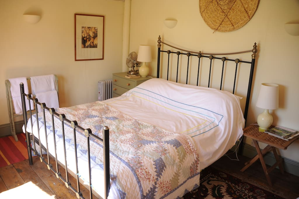 King size bed overlooks deck, rural garden and fields beyond.