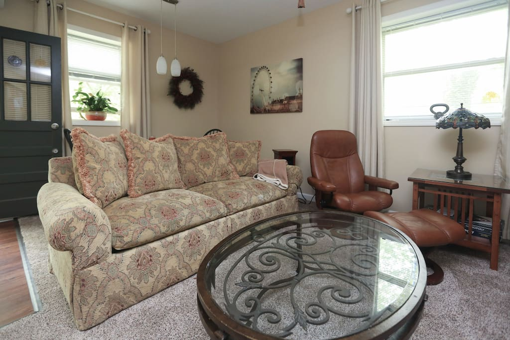 Shows living room seating area. Behind the sofa is a dining table with drop leafs.