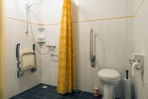 Badkamer met verhoogd toilet en douchestoel.