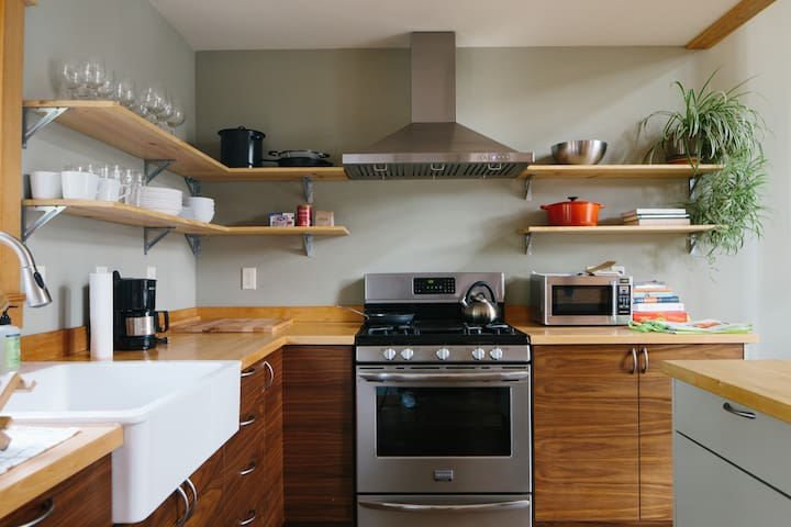 five burner stove with a griddle and massive range hood, ready for anything