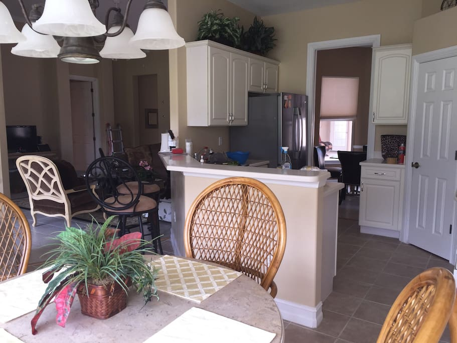 Open kitchen with a view of the golf course. Round kitchen table with 4 wicker chairs & 2 bar stools.
