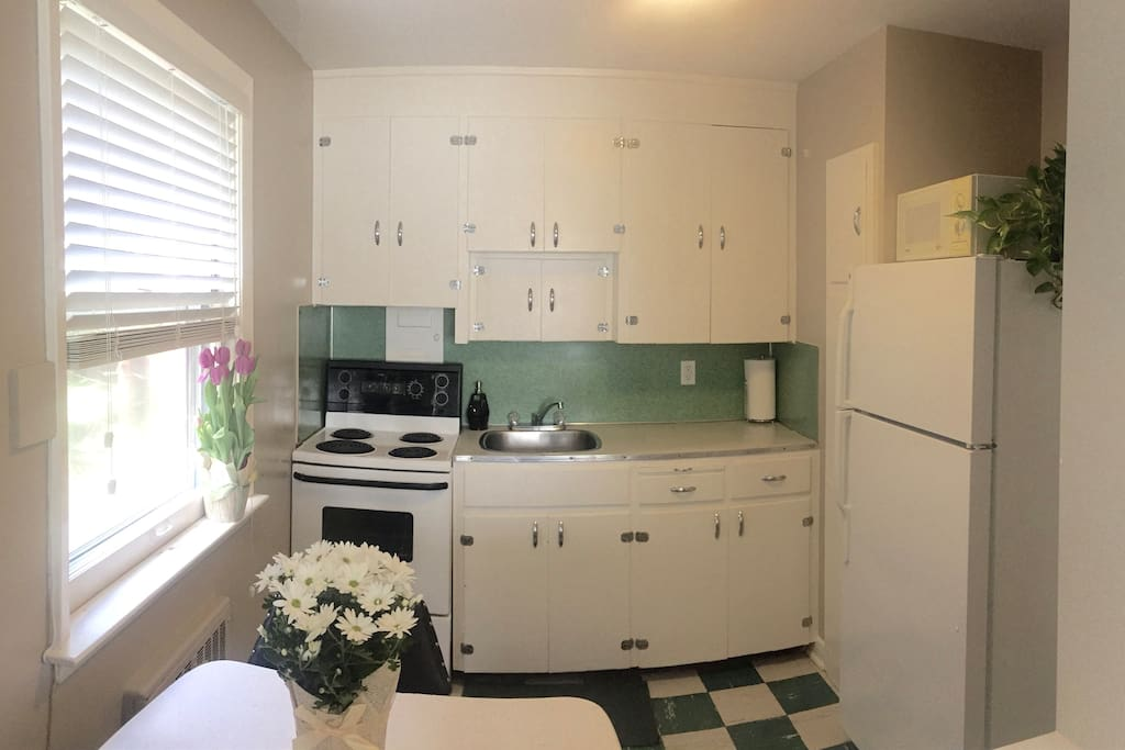 Bright eat-in kitchen, fully stocked with everything you'll need to prepare your own meals in the apartment.