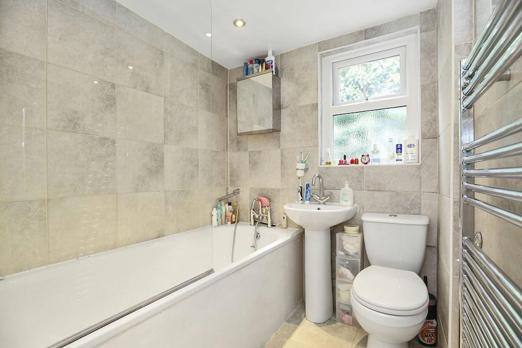Bathroom with shower, bathtub and heated towel rail. Shampoo and shower gel provided