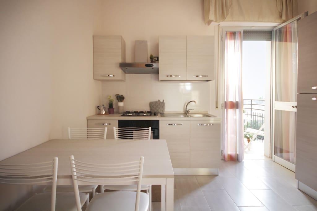 Soggiorno con tavolo e angolo cottura e balconcino.
