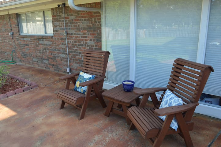 Sitting area next to pergola in backyard