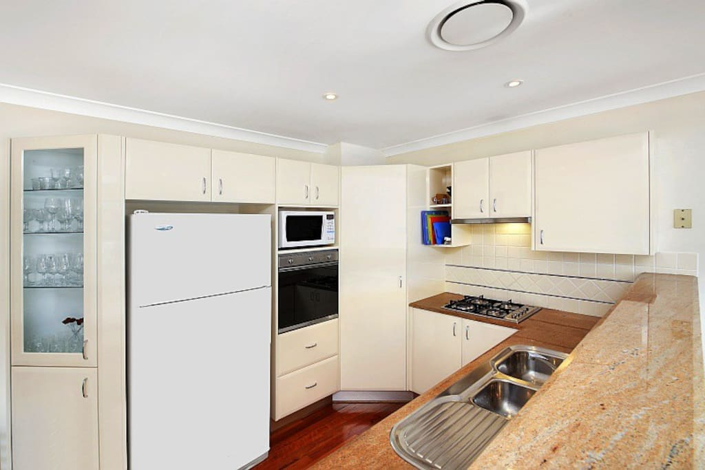 Fully equipped modern kitchen with dishwasher and microwave