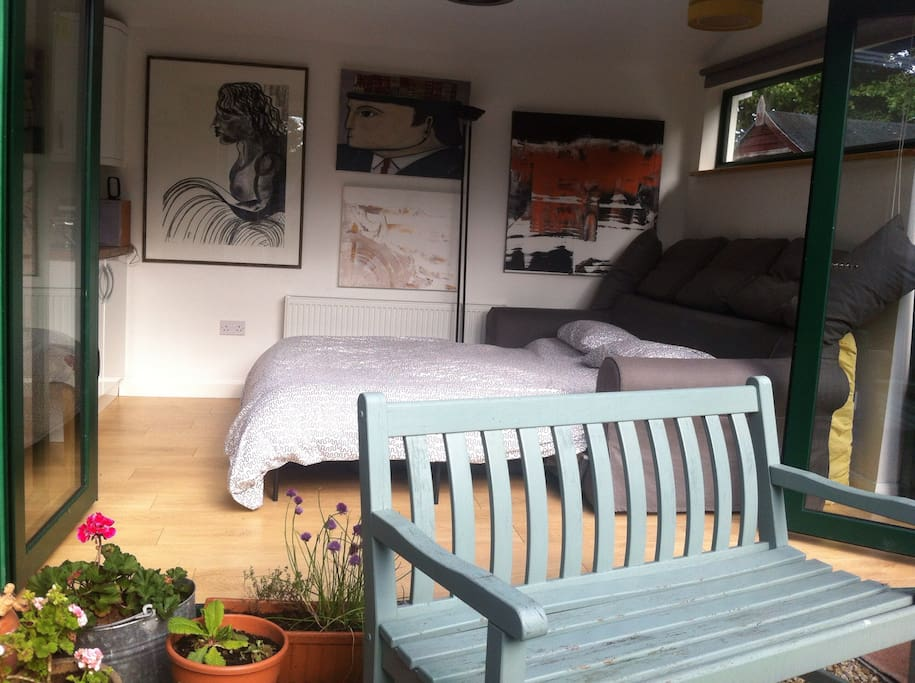 King size sofa bed with doors opening out into a little garden. Original art covering the walls.