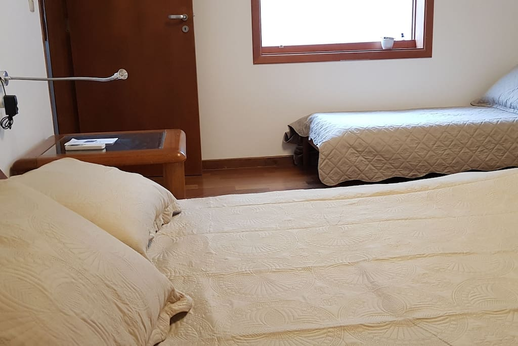 Cama de casal queen size. amplas mesas de cabeceira, luminárias de leitura ultra práticas, cama de solteiro adicional.