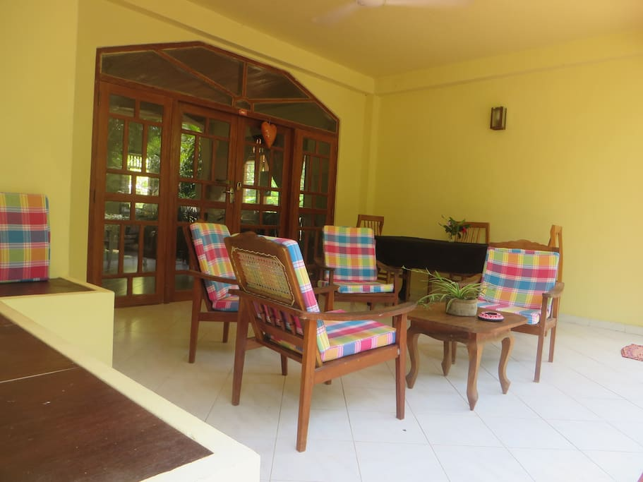 Our spacious & airy verandah.  4 chairs with cushions and a side 'sofa' with cushions against the wall plus 2 tables, 1 x coffee table and 1 x work/dine table.