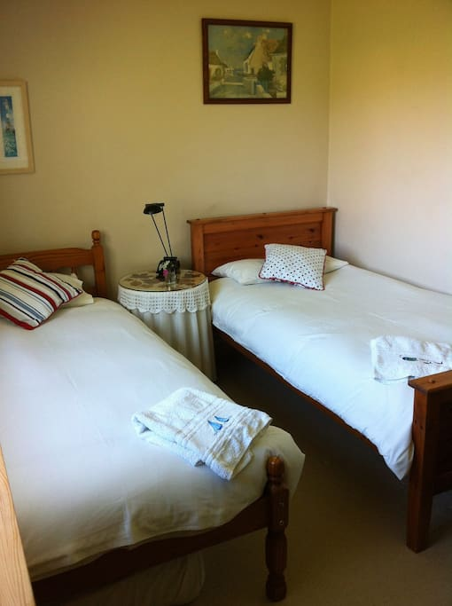 Comfortable, bright, airy twin bedded room.
