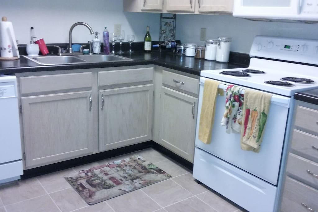 Spacious kitchen with microwave, oven, dishwasher, and refrigerator.