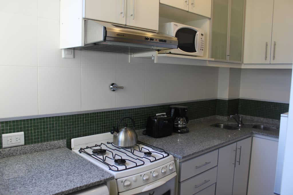 Kitchen with gas range, microwave & fridge/freezer.