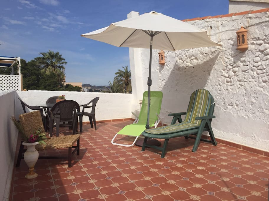 large terrace with loungers and wind up parasol, table and 4 chairs