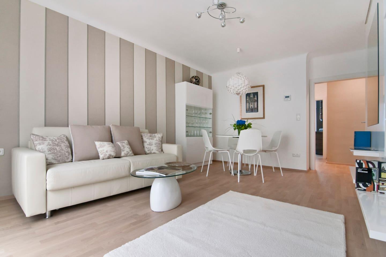 Wohnzimmer; Klimaanlage; Breites Sofa welches zu einem bequemen Doppelbett ausklappbar ist; bietet Schlafkomfort wie in einem Doppelbett; großer neuer Flatscreen; W-Lan; Tischler-Wandverbau