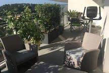 Large et longue terrasse. Deux espaces distincts : salon et repas