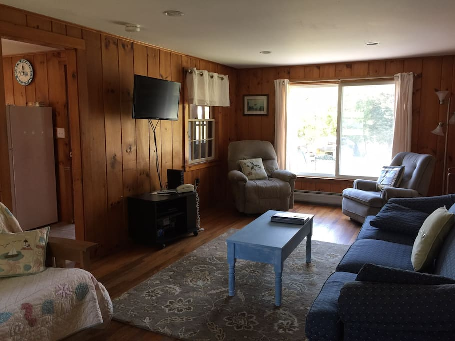 Living room with large window, couch, two reclining chairs and futon.