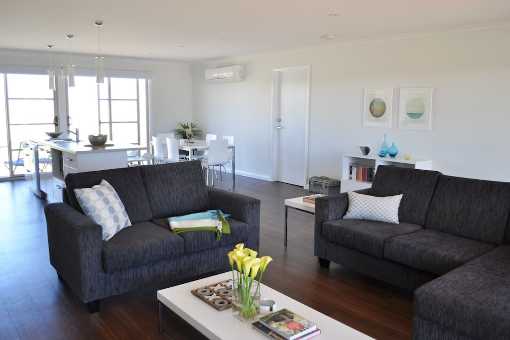 Open plan living, dining and kitchen area with comfortable seating for all guests.