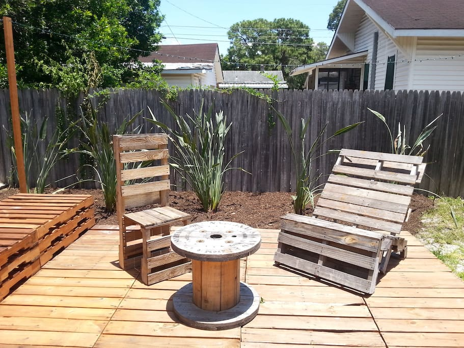 enjoy a drink on the deck in the backyard (made entirely from recycled pallets)
