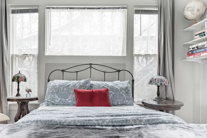 Queen bedroom with tall windows, luxury down duvet, darkening drapes, make-up mirror, hair dryer, books & games for a rainy day.  French lace curtains, antique furniture and family collectibles keep the authentic feel of the Craftsman period. Welcome