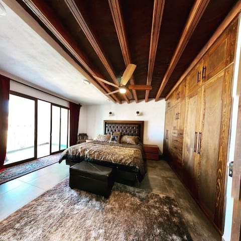 """Master Suit  •King size bed  •Premium Bedding  •Large custom built in wardrobe with hangers. •56"""" flat screen TV •High speed Internet  •Ceiling fan  •Balcony overlooking the city  •Safe •Private Bathroom with all the premium essential items."""