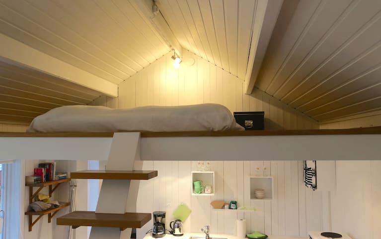 Trappan som leder till sovloftet med del av köket i bakgrunden/The stairs leading up to the sleeping loft with part of the kitchen in the background