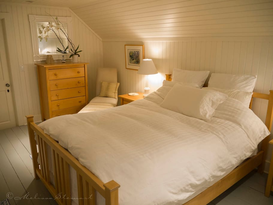 Queen bed with chest of drawers and side tables with lamps.