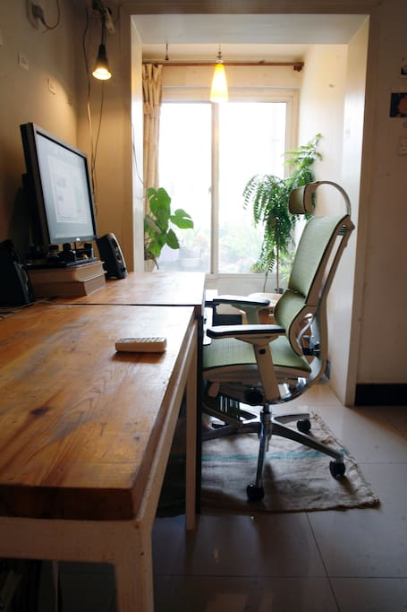 Desk, ergonomic chair and large computer screen for working.