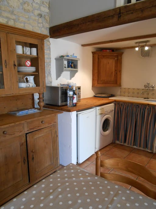 Kitchen area with a fridge, gas cooker, washing machine and microwave.