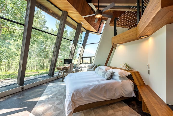 King sized bed in Master Bedroom that is perfectly positioned so that you feel like you're sleeping under the stars but with the comfort of pillows and luxury linens