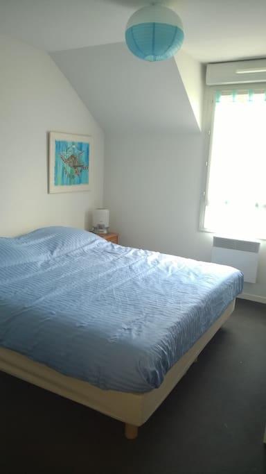 La chambre équipée d'un grand lit confortable