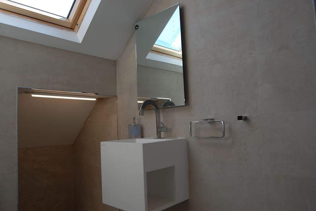 Bathroom with rain shower and a large velux window to allow plenty of light in