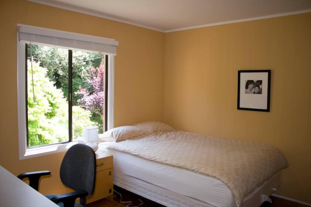 Desk, queen bed with window facing green yard
