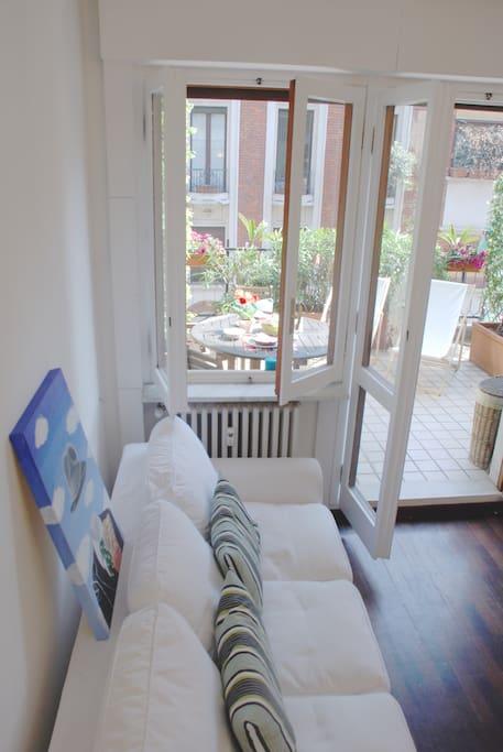 silenzioso soggiorno con il divanoletto e vista terrazzo
