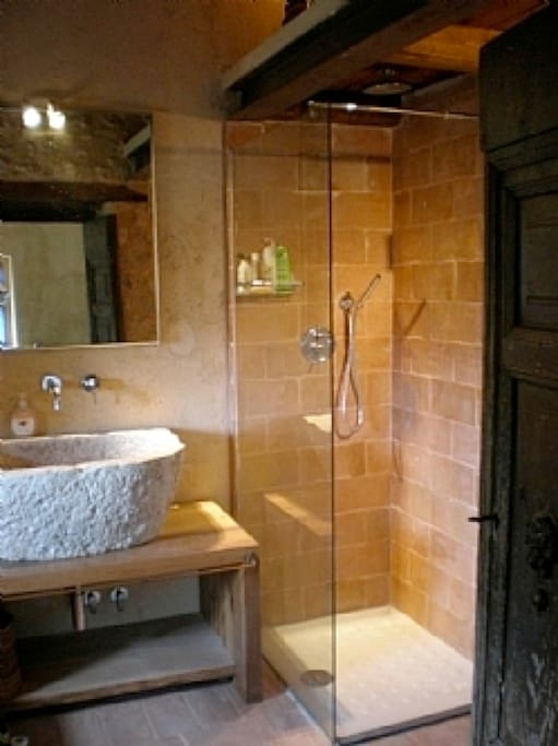 En suite bathroom with modern shower and 300-year-old stone sink.
