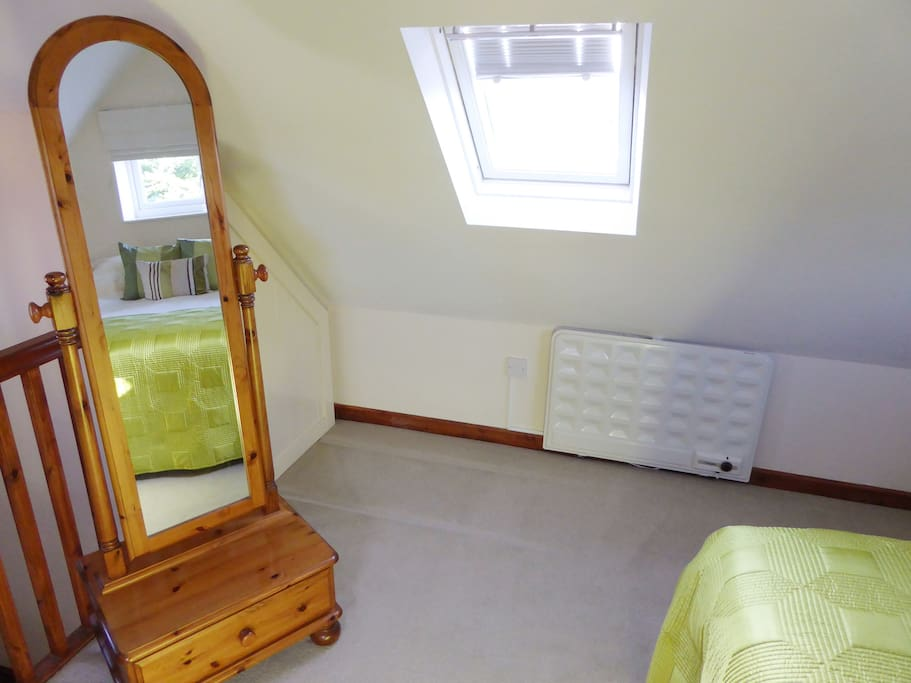The room includes a full-length mirror, wardrobe, and hairdryer.