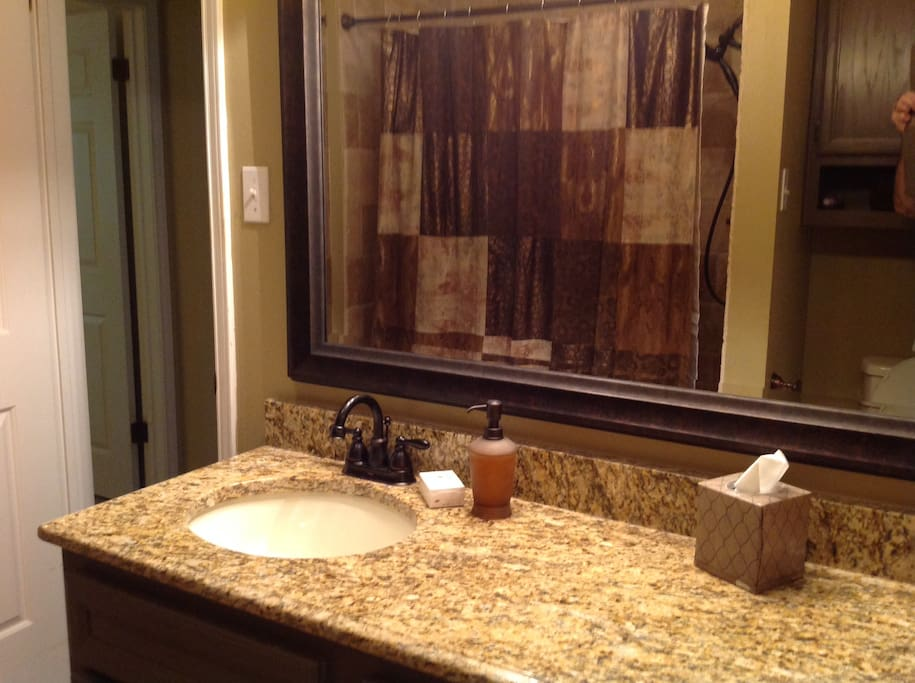 Restroom adjacent to the rooms with large tiled walk-in shower w/ shower bench.