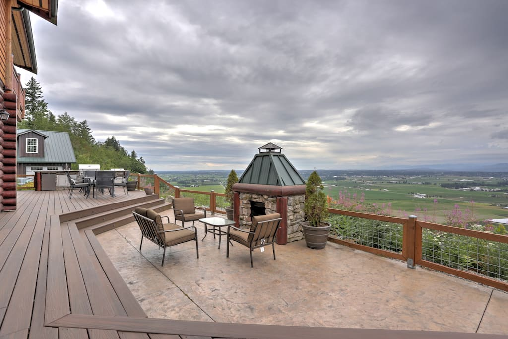 The cliff side deck with a full outdoor kitchen and fireplace offers a cozy and comfortable area to dine, relax, and enjoy the views of the valley far below