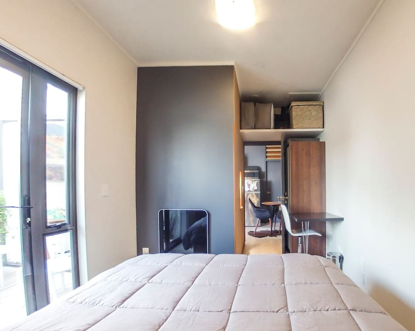 Bedroom has a laptop desk, wardrobe and a heater