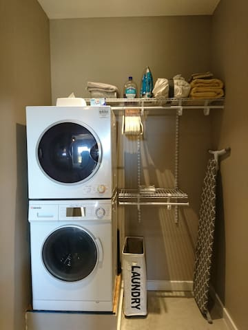 Closet off of bedroom has a washer/dryer, ironing board, iron, laundry basket, extra towels, bath mat, sheets, hand soap, extra pillows, and hangers. We also  provide dryer sheets and a box of laundry detergent on top of dryer for your convinces.