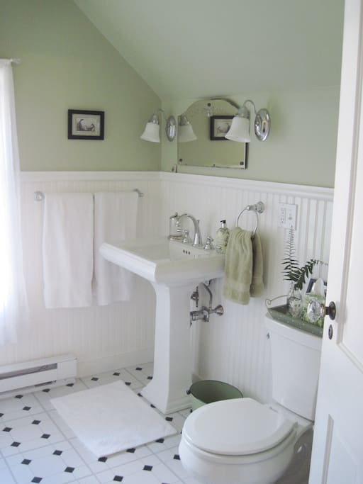 A relaxing private bathroom, en suite, with a small closet for hanging clothes in.