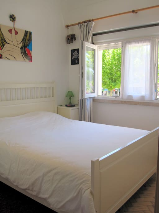 Quite double bed bedroom, facing a park.