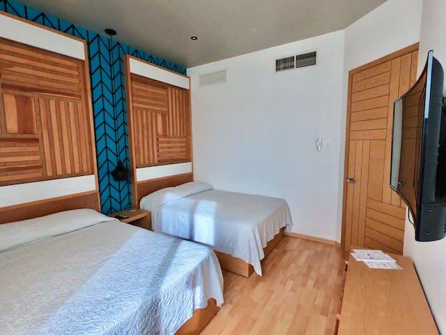 Habitación secundaria con dos camas tamaño matrimonial, clima acondicionado y televisión de pantalla curva