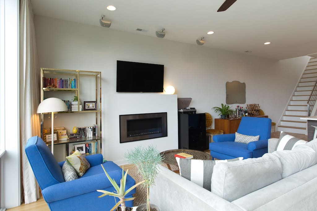Living room area with floor-to-ceiling windows, television with awesome sound system, and a ventless fireplace. Stairs to the rooftop are on the right.