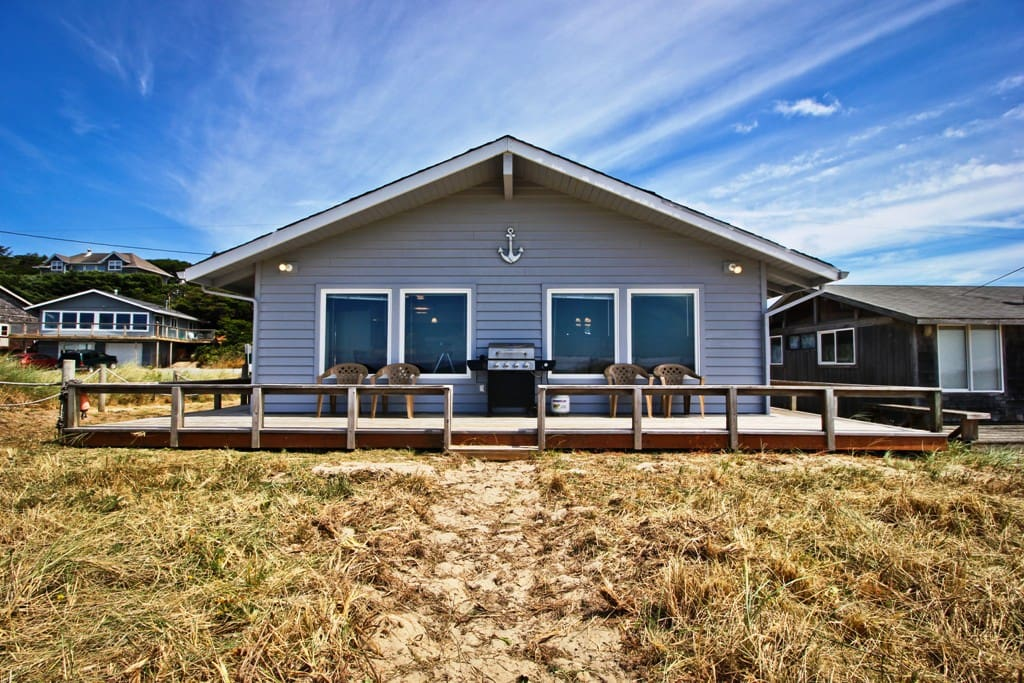 Ocean side of Sandy Shores with a large deck, patio chairs and a gas BBQ