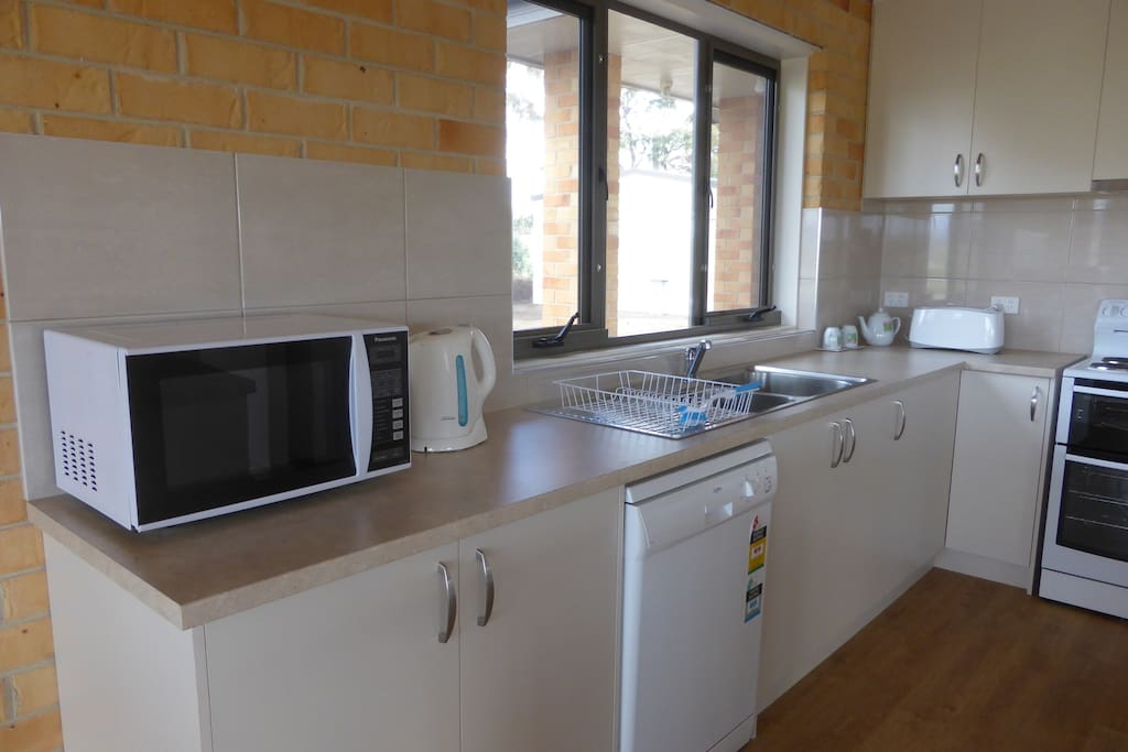 Electric stove, dishwasher and microwave in the well equipped kitchen