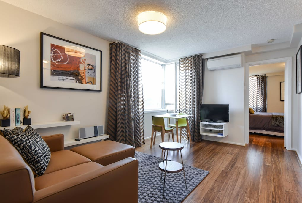 Living area with a comfortable couch, flat screen TV & DVD and aircon in this  StayCentral CBD Vistas serviced apartment