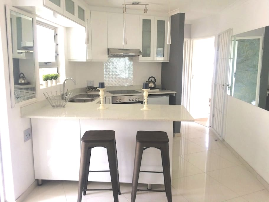 Full kitchen with granite tops, tastefully decorated with a light and modern feel, microwave, stove, oven,  fridge, fully equiped